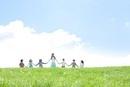草原で手をつなぐ先生と小学生