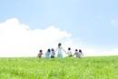草原を歩く先生と小学生の後姿
