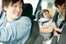 チャイルドシートに乗る赤ちゃんと両親