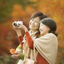 紅葉の写真を撮る2人のシニア女性