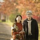 紅葉の前で微笑むシニア夫婦