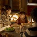 暖炉の前で夕食を食べる家族