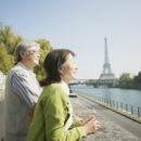 パリの川沿いで微笑むシニア夫婦
