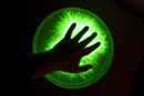 Hand on green illuminated ball