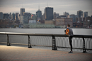 Male Runner Stretching Along Walkway With Manhattan In Backg