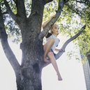 A Young Girl Climbs The Tree In Her Backyard.