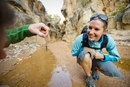 couple looking at lizard while hiking Willis Creek slot cany