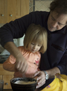 Father and daughter making pankakes