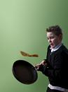 Boy tossing pancake looking really worried