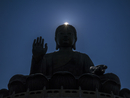 The sun peeks from behind the Tian Tan Buddha (Big Buddha) in Lantau, Hong Kong, China.
