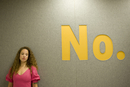 A girl with long curly hair and pink dress poses for a fashion shoot under a felt panel signage interior.