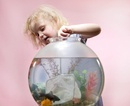 Young girl with fishing net and goldfish bowl