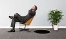 Business man tilting backwards on chair towards hole