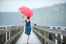 Woman on jetty with red umbrella