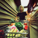 Woman in supermarket with trolley, motion blur