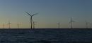 Wind turbines in water against blue sky