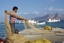 Fisherman sorting his nets, harbour of island of Koufounissia, Lesser Cyclades, Greek Islands, Greece, Europe