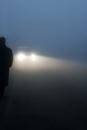 Man in winter coat walking in fog lit by car headlights