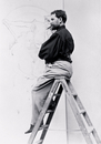 Self-portrait on stepladder, working on the cartoon of the poster 'Imprimerie Cassan Fils', 1896 (b/w photo)