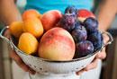 Woman holding colander full of fruit