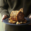 Man holding roast loin of pork with garlic