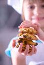 Little girl in chef's hat holding raisin biscuits in her ha