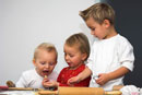 Three children baking biscuits