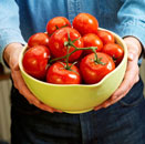 Man holding a bowl of fresh tomatoes