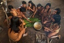Huaorani eating in their house. The meat is chopped up and p