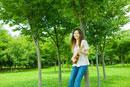 公園の木陰でウクレレを弾く20代女性