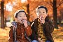 秋の公園で焼き芋を食べる子供