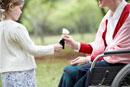 車椅子に座るシニア女性に花をあげる孫