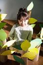 ダンボール製の木の中に立つ少女