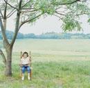 草原の木の下で絵本を読む女の子