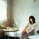 ベッドルームでクッションを抱く20代日本人女性