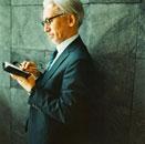 スーツ姿で手帳を開く日本人のシニア男性