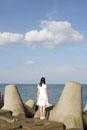 防波堤に立つ白い服の女性後姿