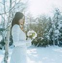 雪の中で花束を持つ日本人の若い女性