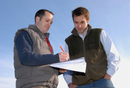 Agronomist and farmer working out field plan, England, Octob