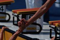 差し伸べた手を握る水泳選手2人の手