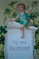 バレンタインのメモの上にまたがるキューピッド