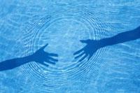 水面に映る2人の手の影