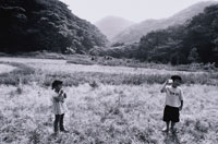 糸電話で遊ぶ2人の日本人の子供達 B&W