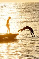 夕景の桟橋から飛び込む子供