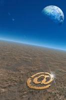地表に描かれたアットマークと星 合成