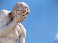 青空と顔に手をあてた男性の彫像 パリ フランス