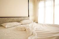 朝日を浴びるリゾートホテルのベッド