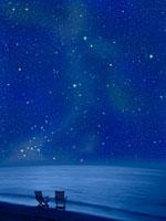浜辺にある二つの椅子と夏の星空