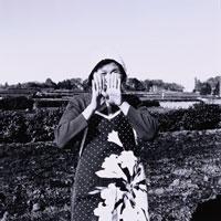 畑で顔を隠す日本人中高年農婦