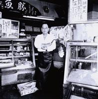 腕組した魚屋の日本人中高年男性